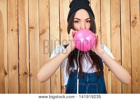 Funky young woman blowing balloon standing against wooden background. Hipster girl with pink balloon.