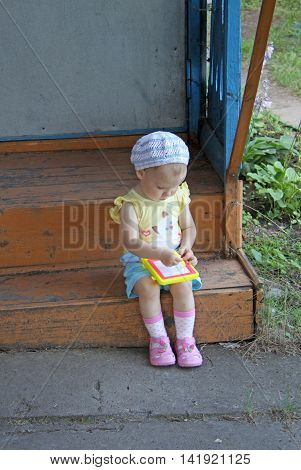 Baby Girl Sitting On The Old Porch