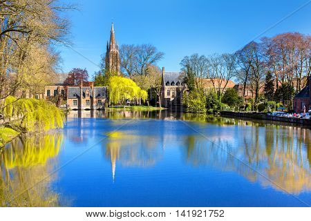 Lake panorama in Bruges, Belgium, church and medieval houses reflection in water, blue sky