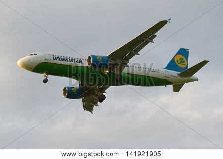 SAINT PETERSBURG, RUSSIA - JULY 03, 2016: Airbus A320-214 (UK-32020) of the company Uzbekistan Airways in cloudy sky