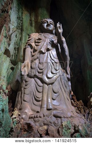 The ancient sculpture of standing Buddha. The cave Tang Chon in the Marble mountains. Da Nang, Vietnam