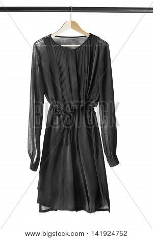 Black chiffon dress on wooden clothes rack isolated over white
