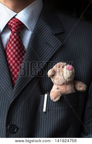 The elegant stylish businessman keeping cute teddy bear in a his breast suit pocket. Formal negotiations concept