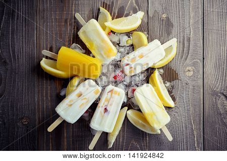 refreshing fruit popsicle on ice background with pieces of a lemon and apple toning