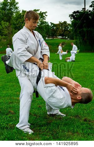 Miskolc Hungary - August 2. 2016: Athletes perform abdominal exercises holding partner of the belt during the international summer training camp for Kyokushin Karate.