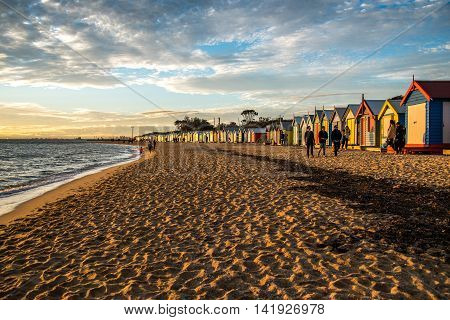 MELBOURNE AUSTRALIA - JULY 18 2016 : Tourists walk pass colorful bathing boxes at Brighton Beach near Melbourne Australia.
