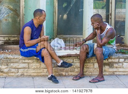 HAVANA CUBA - JULY 18 : Unidentified men play Checkers on the street on July 18 2016 in Havana Cuba. Checkers is one of the most popular games in Cuba