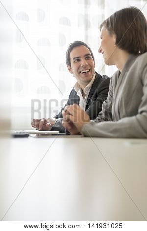 Business colleagues smiling at one another with focus to a young man with his finger on a tablet computer chatting to a female coworker low angle view across the table with copy space.