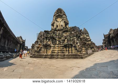 ANGKOR WAT CAMBODIA - JANUARY 27 2015: Unidentified tourists at Angkor Wat temple in Cambodia. Angkor Wat is the largest Hindu temple complex and religious monument in the world