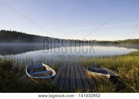 Moored boats in Lake Tevsjon near the Swedish village Ljusnedal early in the morning