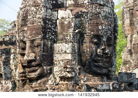 Huge carved Buddha faces of Bayon temple at Angkor Wat complex Siem Reap Cambodia