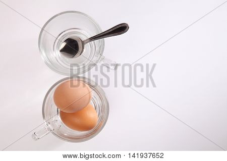 half boiled eggs in a glass cup on the white background