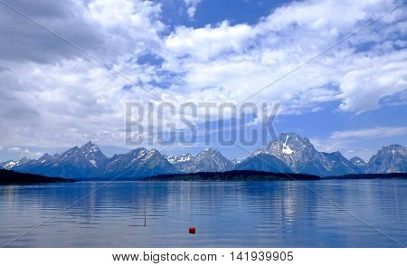 Reflection of mountains in calm water. Jackson lake in Grand Tetons National Park Wyoming USA.