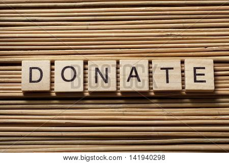 text of DONATE on cubes. Wooden abc