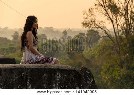 ANGKOR WAT CAMBODIA - JANUARY 28 2015: Young beautiful woman watching sunset at the top of Phnom Bakheng at Angkor Cambodia