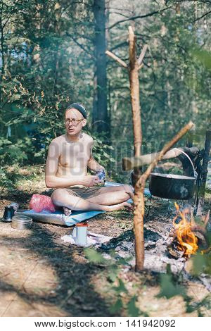 Young male hipster prepares coffee on a fire in the forest. Rest in the woods