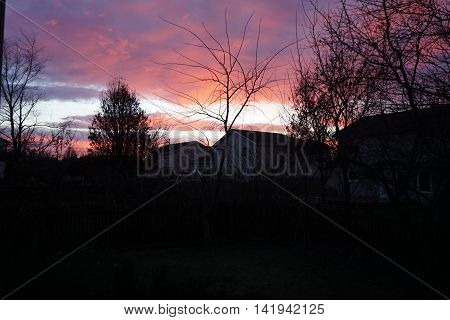 A red sky at dawn, in a residential area of Joliet, Illinois, during December.