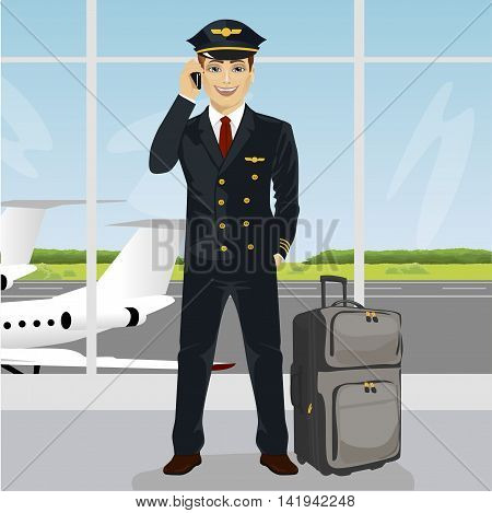 Young pilot talking on the phone with luggage in front of an airport observation deck