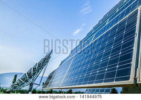 Blue photovoltaic solar panels and sky background