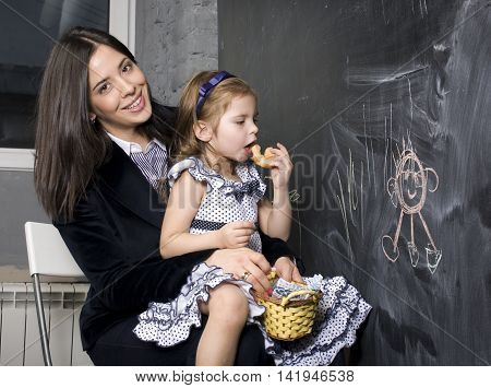 teacher with pupil in classroom at blackboard writting, mother and daughter first time to school, lifestyle people concept
