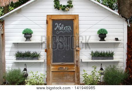 Plants on shelves, growing in a garden, with an antique wood door propped against a white wall of shed