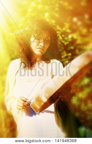 beautiful shamanic girl playing on shaman frame drum on background with leaves and flowers. solar light effect and dreamy blur effect