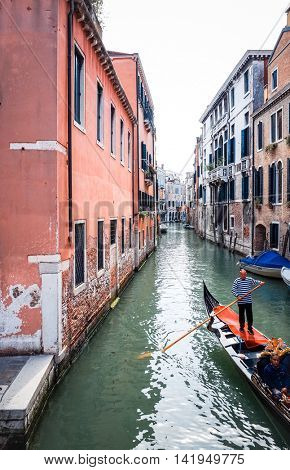 VENICE, ITALY - March 26, 2016.Tourists on water street with Gondola in Venice on May 26, 2015. its entirety is listed as a World Heritage Site, along with its lagoon.May 26 VENICE, ITALY
