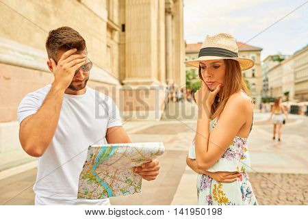 A beautiful young woman upset to her boyfriend who is looking at a map for a way at the St. Stephens Basilica in Budapest, Hungary.