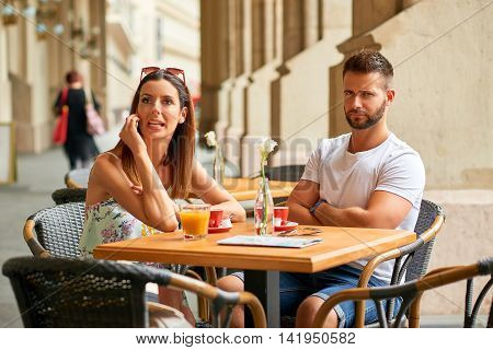 A handsome guy is upset to his beautiful girlfriend because she is talking on the phone while they are having a coffee at a table on a terrace in Budapest, Hungary.