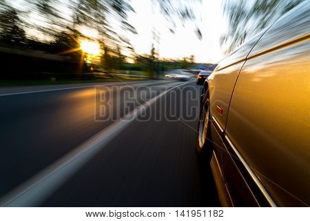 Car ride on road in sunny weather, motion blur. Camera close up to road.