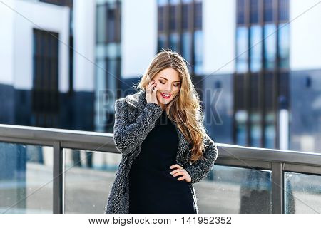 Pleasant modern attractive business young woman talking on the phone standing on office backgraund
