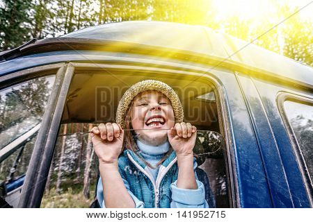Cheerful little girl looks out the car window.
