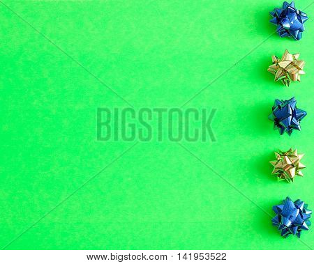 A row of blue and gold gift bows isolated on a green background