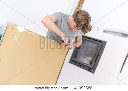 Single young adult man in gray short sleeved shirt cutting open a large brown box with blade.