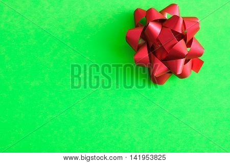 A red gift bow isolated on a green background