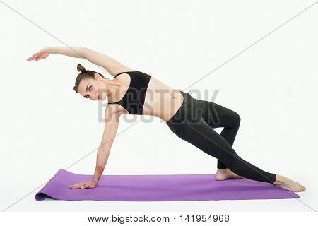 Young Brunette Woman Doing Pilates Exercises On Mat Isolated