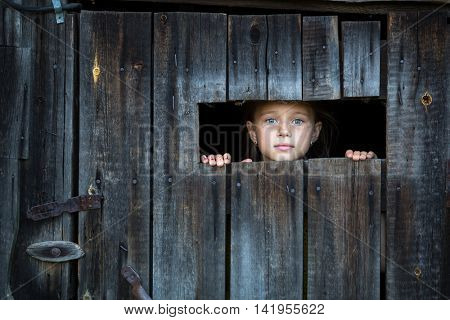Little girl peeking through from the window at doors. Locked in the shed.