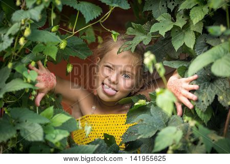 Little girl hamming and showing tongue peeking out from behind the greenery.