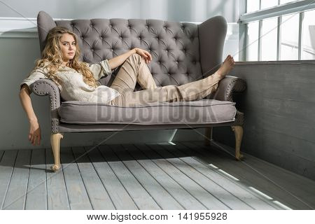 Stylish barefoot girl lies on the sofa at home and looks into the camera with smile. She wears olive shirt and beige pants. Left hand is on the left knee, right hand hangs down. Indoors. Horizontal.