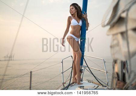 Pretty girl stands on the yacht in a white swimsuit and holds the mast on the background of the sea and the sky. She looks to the right with parted lips. Outdoors. Horizontal.