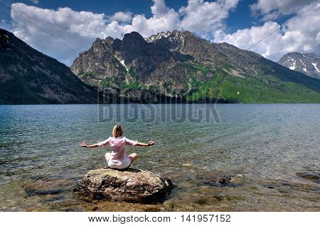 Woman sitting in yoga pose by lake. Jenny Lake in Grand Tetons National Park Jackson Wyoming.