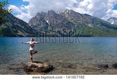 Woman in yoga pose by lake and mountain. Jenny Lake in Grand Tetons National Park Jackson Wyoming.
