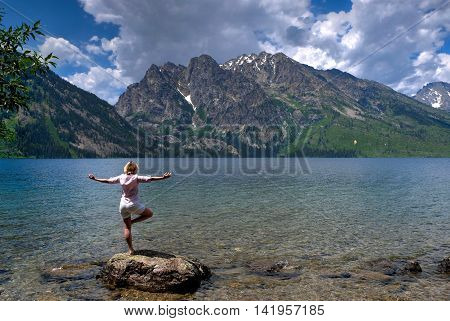 Woman exercising by lake and mountains. Jenny Lake in Grand Tetons National Park Jackson Wyoming.