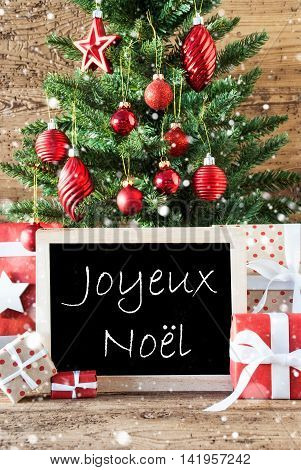 Colorful Christmas Card For Seasons Greetings. Tree With Balls And Snowflakes. Gifts Or Presents In The Front Of Wooden Background. Chalkboard With French Text Joyeux Noel Means Merry Christmas