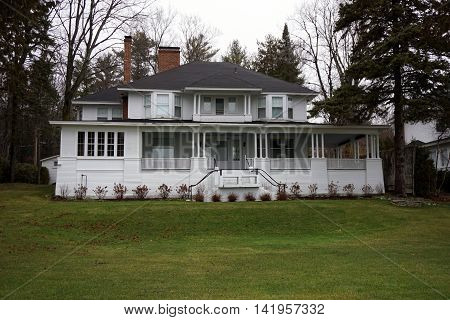 WEQUETONSING, MICHIGAN / UNITED STATES - DECEMBER 22, 2015: A large elegant white home, with a wraparound porch and a balcony, on Beach Road in Wequetonsing, Michigan.