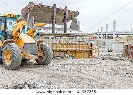 Excavator with inserted forklift is loaded with metal bars for concrete reinforcement.