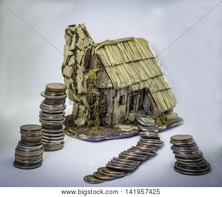 Concept for home mortgage and unrealistic debt - coins stacked up around house and leading to front door with coin trail pathway