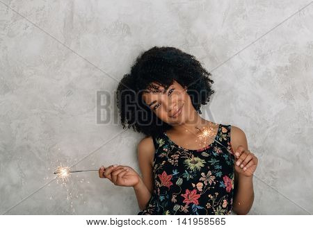 African American young woman playing with sparklers