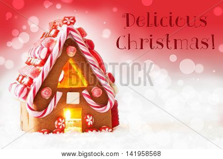 Gingerbread House In Snowy Scenery As Christmas Decoration. Candlelight For Romantic Atmosphere. Red Background With Bokeh Effect. English Text Delicious Christmas