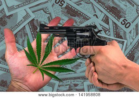 marijuana gun in his hands on the dollars background
